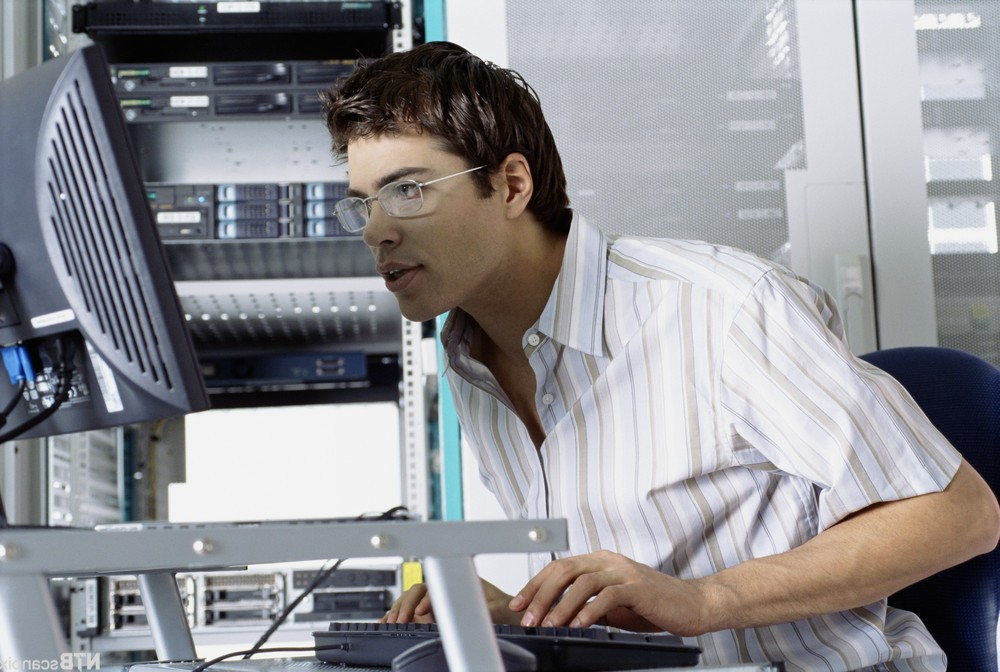 IT Worker Using Computer in Server Room --- Image by © Royalty-Free/Corbis